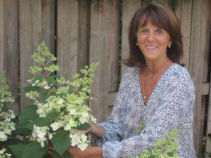 image de Danielle Beauchamp, naturopathe agréée dans son jardin avec un hydrangée