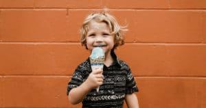 jeune garçon blond et souriant tenant un cornet de crème glacée