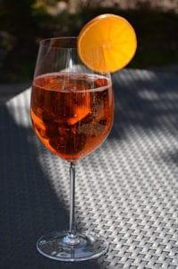 Spritzer ambré dans une coupe à vin avec une tranche d'orange en décoration