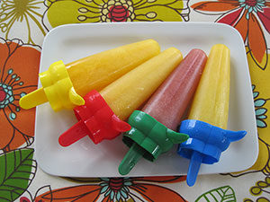 sucettes glacées de couleurs orange et mauves placées dans une assiette blanche