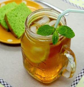 thé glacé maison dans un verre style pot masson avec tranche de citron, feuille de menthe et paille
