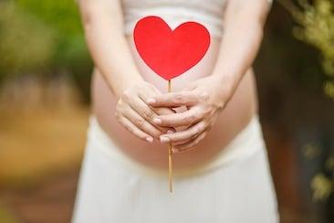bédaine de femme enceinte tenant un bâton avec un coeur rouge en carton