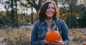 femme souriante tenant une citrouille